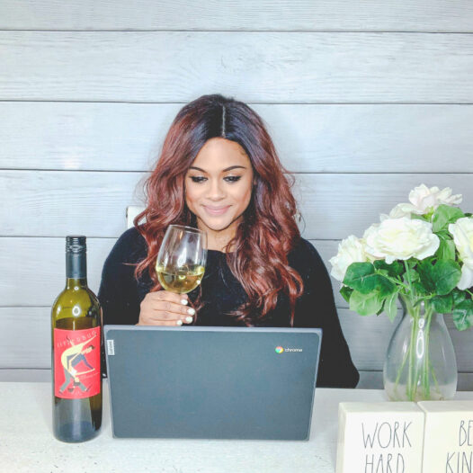 woman sipping wine at her computer